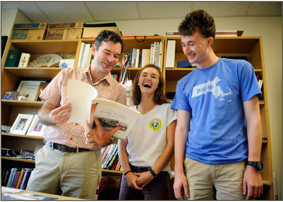 Assistant professor Matthew Eckelman shares the yearbook from his time as a high school student in the Young Scholars Program with current scholars MaryBeth Rockett and Louis Sokolow.